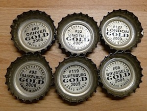 six bottle tops - all show Sam Adams awards around the world